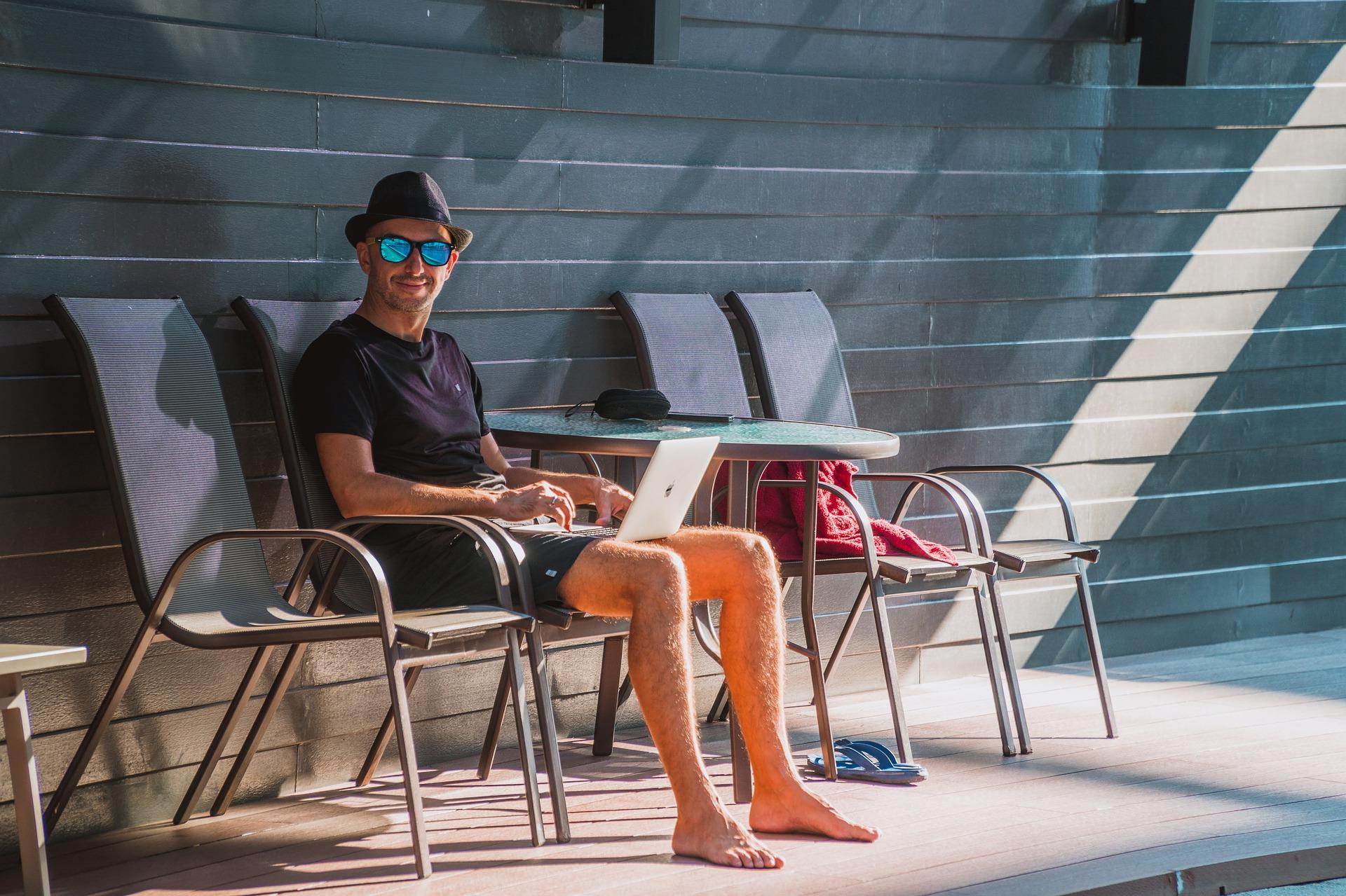 Mann mit Laptop am Pool